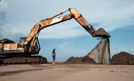 Het graafwerktuig bouwt golfbreker bij strand Stock Foto's