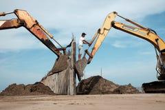 Het graafwerktuig bouwt golfbreker bij strand Stock Afbeeldingen
