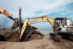Het graafwerktuig bouwt golfbreker bij strand Royalty-vrije Stock Foto