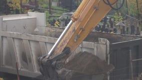 Het graafwerktuig en de vrachtwagen maken grond leeg stock videobeelden