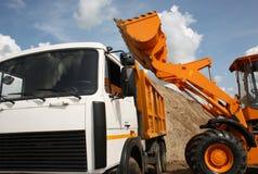 Het graafwerktuig giet zand aan kipwagen Royalty-vrije Stock Foto's