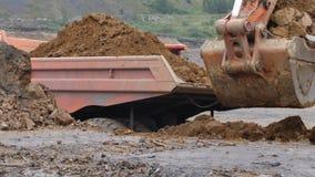 Het graafwerktuig graaft de grond in close-up Het graafwerktuig laadt het lichaam van een stortplaatsvrachtwagen De harkenklei va stock videobeelden