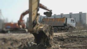 Het graafwerktuig laadt de klei in oranje stortplaatsvrachtwagen stock video