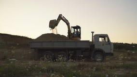 Het graafwerktuig laadt een vrachtwagen stock videobeelden