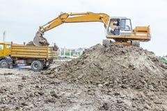 Het graafwerktuig laadt een vrachtwagen op bouwterrein Stock Fotografie