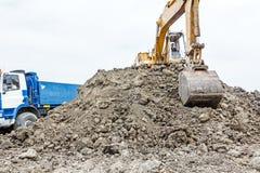 Het graafwerktuig laadt een vrachtwagen op bouwterrein Royalty-vrije Stock Foto