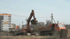 Het graafwerktuig laadt grond in een vrachtwagen bij bouw stock footage