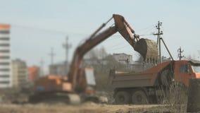 Het graafwerktuig laadt grond in een vrachtwagen bij bouw stock video