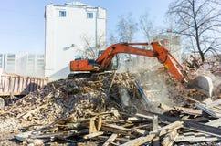 Het graafwerktuig laadt huisvuil van vernietigd huis Stock Afbeeldingen