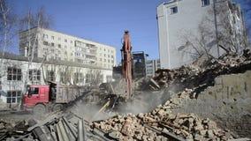Het graafwerktuig laadt huisvuil van vernietigd huis stock footage