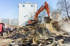 Het graafwerktuig laadt huisvuil van vernietigd huis Stock Foto