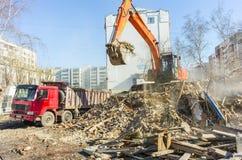 Het graafwerktuig laadt huisvuil van vernietigd huis Stock Fotografie
