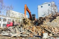 Het graafwerktuig laadt huisvuil van vernietigd huis Stock Foto's