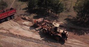 Het graafwerktuig laadt het zand in de vrachtwagen De arbeiders maken de manier stock footage