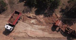 Het graafwerktuig laadt het zand in de vrachtwagenarbeiders maakt de manier stock footage