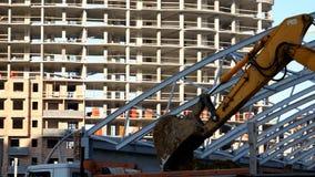 Het graafwerktuig laadt het zand met een gietlepel in het lichaam van een vrachtwagen op de bouwwerf In aanbouw de bouw stock footage