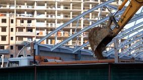 Het graafwerktuig laadt het zand met een gietlepel in het lichaam van een vrachtwagen op de bouwwerf In aanbouw de bouw stock video