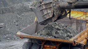 Het graafwerktuig vult stortplaatsvrachtwagen De close-up van het emmergraafwerktuig laadt stenen in lichaam van stortplaatsvrach stock videobeelden