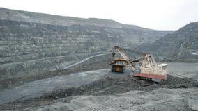 Het graafwerktuig vult stortplaatsvrachtwagen met aarde in open kuil De zware machineswerken in mijnbouw in open kuil stock foto's