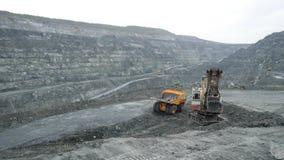 Het graafwerktuig vult stortplaatsvrachtwagen met aarde in open kuil De zware machineswerken in mijnbouw in open kuil stock afbeelding