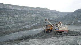 Het graafwerktuig vult stortplaatsvrachtwagen met aarde in open kuil De zware machineswerken in mijnbouw in open kuil royalty-vrije stock afbeeldingen