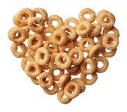 Het graangewas van Cheerios in een hartvorm die op wit wordt geïsoleerdw Stock Fotografie