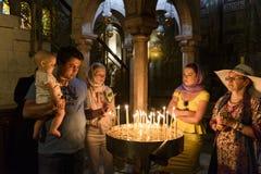 Het grafgewelfpelgrims die van heilige met kaarsen bidden Stock Foto