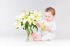 Het grappige baby spelen met leliebloemen Stock Afbeelding