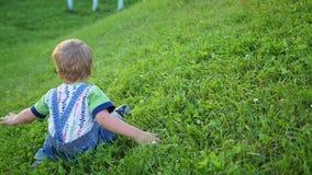 Het grappige baby spelen op het gras Rolling neer van de helling Pret in openlucht stock videobeelden