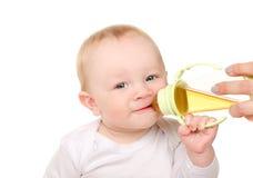 Het grappige babyjongen drinken van fles Stock Afbeeldingen