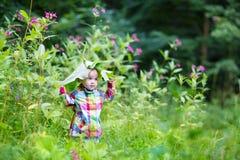 Het grappige babymeisje spelen gluurt een boe-geroep in een park onder reusachtige bladeren Stock Afbeelding