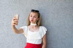 Het grappige blonde stellen met smartphone Stock Afbeeldingen