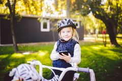 Het grappige blonde van het kind Kaukasische meisje in een fietshelm dichtbij een purpere fiets met een mand in buiten het park o stock foto's