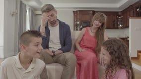 Het grappige broer en zuster vechten in de voorgrond, de verwarde moeder en de vaderzitting op de laag op de achtergrond stock footage