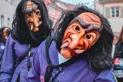 Het grappige Carnaval-cijfer in violet kostuum onderzoekt de camera stock afbeelding