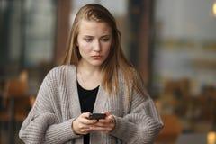 Het grappige droevige jonge het meisje van het close-upportret denken binnen telefoneert kijken die omhoog het zien van slechte n stock afbeeldingen