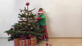Het grappige elf schikt ornamenten in Kerstboom, gelukkige kind wachtende Kerstmis stock footage