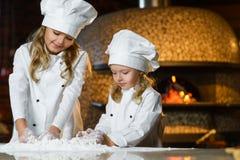 Het grappige gelukkige de breedtemeisje van de chef-kokjongen koken bij Stock Afbeelding