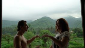 Het grappige gelukkige paar die op het balkon met mooie bergmening, mensen in liefde dansen, geniet van hun leven, emoties stock videobeelden