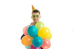 Het grappige grote jonge jonge geitje houdt zich veel gekleurde ballen is Stock Foto