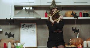 Het grappige heks spelen charismatisch voor de camera op Halloween-nacht op de keuken, heeft zij een Aziatisch gezicht en stock videobeelden