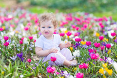 Het grappige het lachen baby spelen met eerste de lentebloemen royalty-vrije stock afbeeldingen