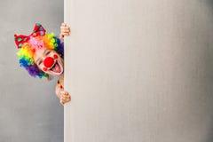 Het grappige jong geitjeclown binnen spelen stock foto