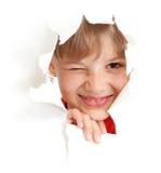 Het grappige jonge geitje knipoogt oog in gescheurd document geïsoleerdd gat Stock Afbeelding