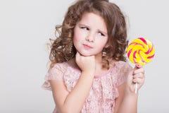 Het grappige kind eet suikergoedlolly, meisje die snoepjes, studio eten Stock Afbeeldingen