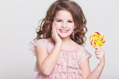 Het grappige kind eet suikergoedlolly, meisje die snoepjes, studio eten Stock Foto