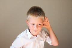 Het grappige kind luisteren stock afbeeldingen