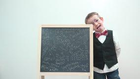 Het grappige kind met oogglazen en eenvormig maakt gezichten het dichte schoolbord, pret van het leren maakt stock footage