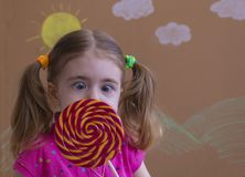 Het grappige kind met suikergoedlolly, gelukkig meisje die grote suikerlolly, jong geitje eten eet snoepjes Stock Foto's