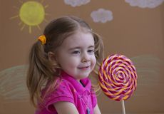 Het grappige kind met suikergoedlolly, gelukkig meisje die grote suikerlolly, jong geitje eten eet snoepjes Royalty-vrije Stock Afbeeldingen